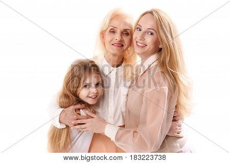 What love is. Granddaughter is hugging her mother and granny. They are looking at camera with happiness in their eyes. Portrait. Isolated