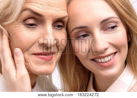 Joyful mother and daughter are looking aside with bright smile. Portrait