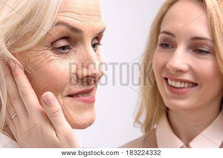 Cheerful daughter is putting her hand on face of old mother. They are smiling. Portrait. Isolated