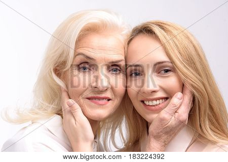 Happy idyll. Smiling mother and daughter are putting hands on faces of each other. Portrait. Isolated