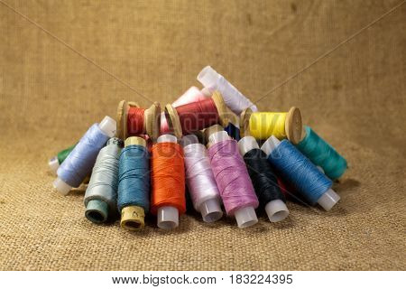A lot of bobbins with colorful threads lay on the cloth