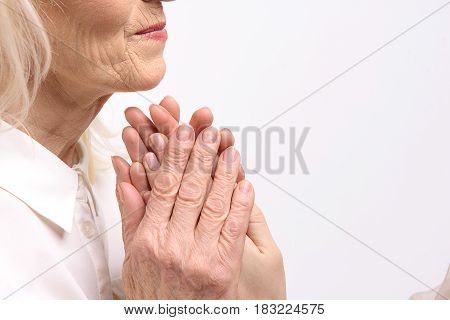 Matured lady is holding palms of young woman. Isolated. Copy space on right side