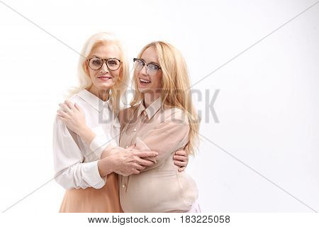 Old woman in spectacles is hugging young pregnant lady with eyewear on her face. Portrait. Isolated
