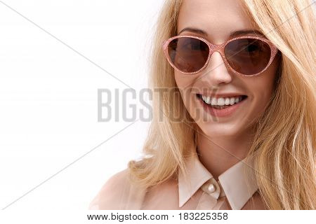 Hilarious smiling lady is wearing sunny glasses and looking at camera with joy. Copy space on left side. Portrait. Isolated