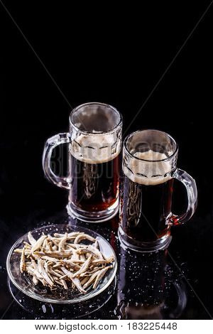 Image of beer mugs with anchovies on empty background