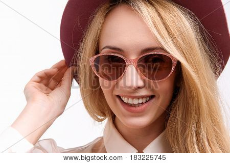Stylish happy lady wearing hat and sunglasses is looking at camera with bright smile. Portrait. Isolated