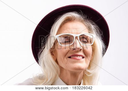 Fashioned old lady in hat is standing with closed eyes and bright smile. Portrait. Isolated