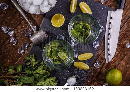 Set of accessories and ingredients for making cocktails arranged on wooden background with black board