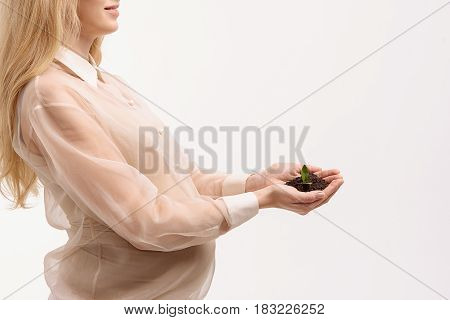 Life beginning. Pregnant woman holding handful of soil. Isolated. Copy space on right side