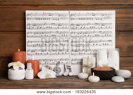 Beautiful composition of spa accessories and musical notes on brown wooden background