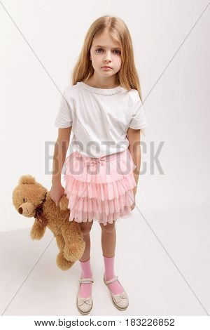 Attentive little girl is holding soft toylike bear and looking at camera with seriousness. Portrait. Isolated