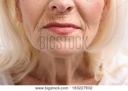 Time cannot regret anyone. Wrinkled female face. Close up