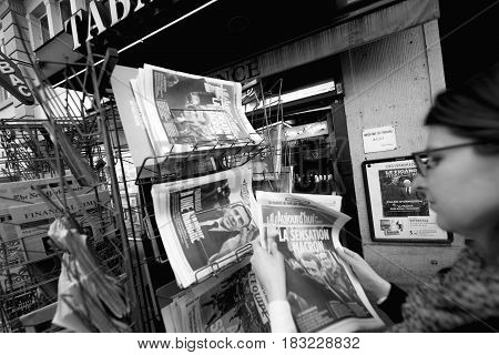 PARIS FRANCE - APRIL 24: Woman buy looks at press kiosk at French newspaper Aujord'hui with pictures of French Presidential election candidates Emmanuel Macron a day after first round of French Presidential election on April 23 2017