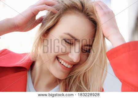 Life is great. Portrait of happy blond girl enjoying walk outdoors. She is touching her hair and smiling. Her eyes are closed with enjoyment