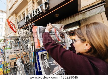 PARIS FRANCE - APRIL 24: Woman buy looks at press kiosk at French newspaper Liberation with pictures of French Presidential election candidates Emmanuel Macron a day after first round of French Presidential election on April 23 2017