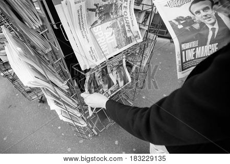 PARIS FRANCE - APRIL 24: Woman buy looks at press kiosk at French newspaper with pictures of French Presidential election candidates Emmanuel Macron Marine Le Pen a day after first round of French Presidential election on April 23 2017