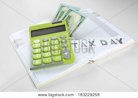 Calculator with money and notebook on white background. Tax concept