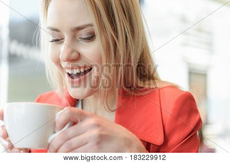 Portrait of joyful young woman drinking coffee in cafeteria. She is looking into the cup with excitement and smiling