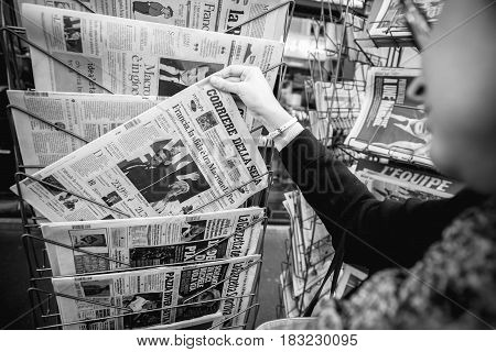 PARIS FRANCE - APRIL 24: Woman buy looks at press kiosk at Italian Corriere della Sera newspaper with pictures of French Presidential election candidates Emmanuel Macron Marine Le Pen a day after first round of French Presidential election on April 23 201
