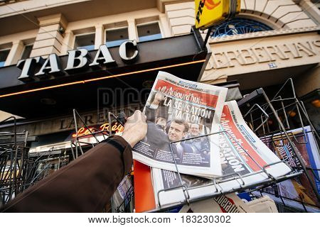 PARIS FRANCE - APRIL 24: Man buy looks at press kiosk at French newspaper Aujord'hui with pictures of French Presidential election candidates Emmanuel Macron a day after first round of French Presidential election on April 23 2017