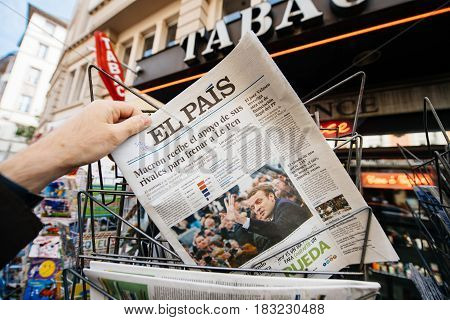 PARIS FRANCE - APRIL 24: Man buy looks at press kiosk at Spanish El Pais newspaper with pictures of French Presidential election candidates Emmanuel Macron Marine Le Pen a day after first round of French Presidential election on April 23 2017