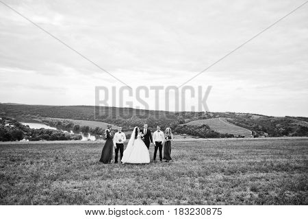 Wedding Couple With Bridesmaids And Best Mans Walking Outdoor.