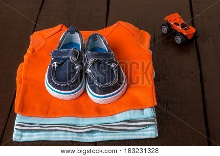 Folded Blue And Orange    Bodysuit With Boat Shoes On It On  Wooden Background. Diaper For Newborn B