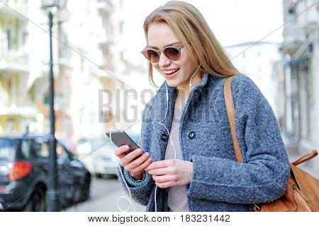 Excited blond girl is choosing music to listen to from her playlist in phone. She is standing on street and smiling