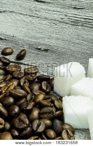 coffee grains and sugar on grunge wooden background