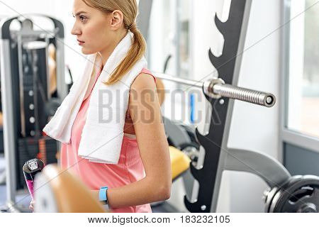 Side view serious woman locating near barbell. She finishing exercise