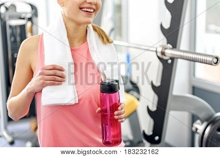 Smiling female drinking water after hard train in fitness center