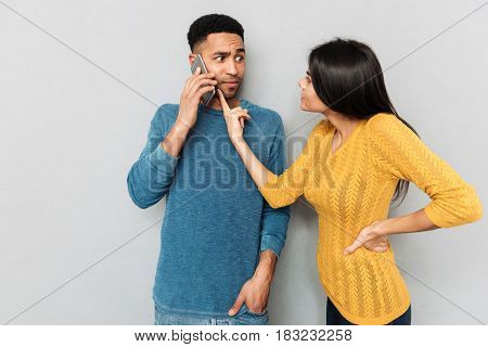Displeased woman pointing at phone of her husband with claim isolated
