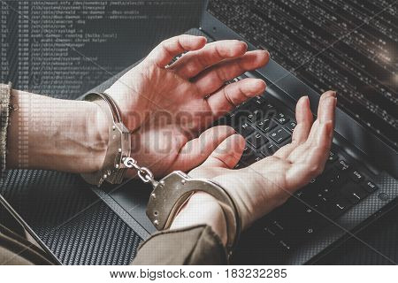 Arrested hacker with hands behind in handcuffs on the laptop keyboard and digital code around. Cyber crime concept. Matt toning.