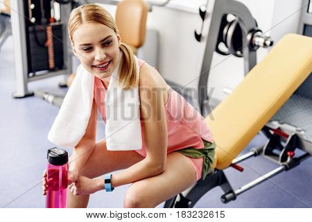 Outgoing girl feeling fatigue after good workout in gym. She keeping blender bottle in arms while sitting on weight bench