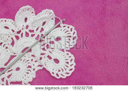 White vintage crochet doily. Cotton yarn for knitting and crochet hook on the pink plush background