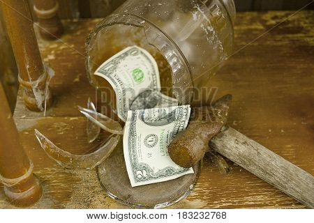 Smashed jar as a money pot with US currency laid next to the hammer