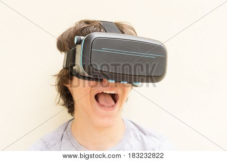Surprized Teenager wearing VR virtual realty glasses close up