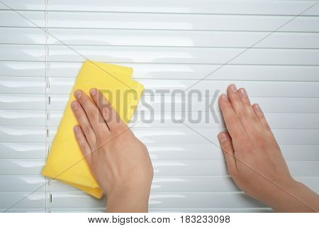 Female hands washing white jalousie on  window, closeup