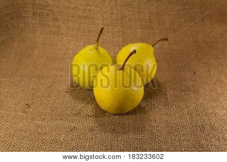 Ripe yellow pears lie on the cloth.