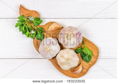 Garlic Cloves And Garlic Bulb On A Wooden Board On A White Background. Top View