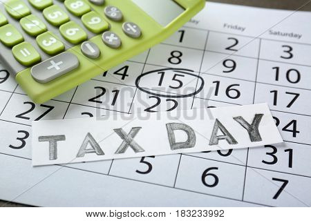 Card with text TAX DAY and calculator on calendar, closeup