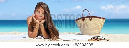 Woman relaxing on beach vacation summer holidays banner with on sky and blue ocean. Beautiful Asian girl lying down on towel with flips flops and beach bag tanning. Sun hair and skin care concept.
