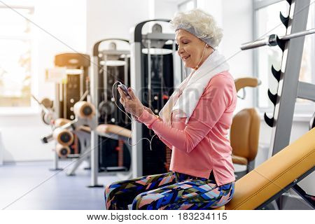 Side view female beneficiary expressing happiness while looking at mobile. She sitting on weight bench in gym. Sport concept