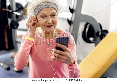 Portrait of grandmother expressing gladness while hearing song and watching at cellphone in fitness center