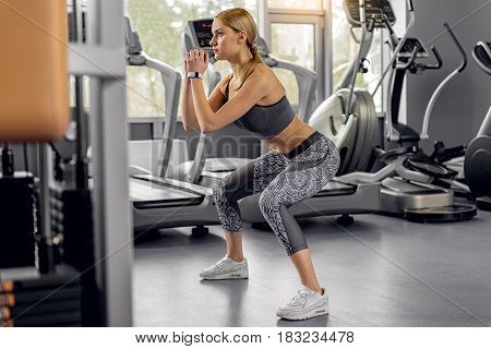 Side view young woman demonstrating composure while squatting in modern gym