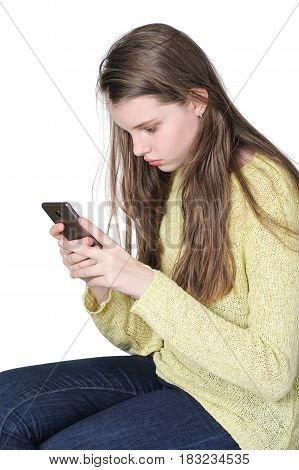 A Young Cute Girl Looks Closely Into Her Smartphone.