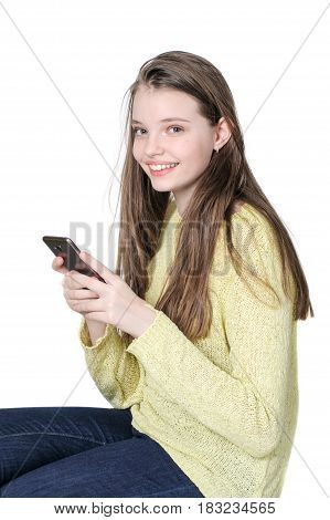 Young Smiling Girl Is Holding A Smartphone In Her Hands..