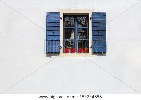Blue window shutters on the white facade