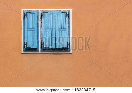Blue wooden window shutters on the orange facade