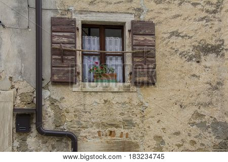 Brown wooden window shutters on the old stone house